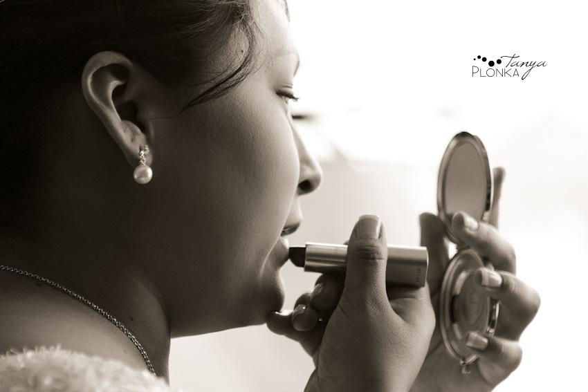 Bride applies lipstick