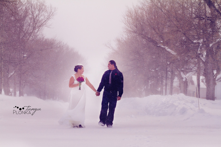 Bride and groom walking through snow in Waterton