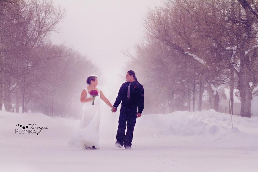 Bride and groom walking through snow in Waterton