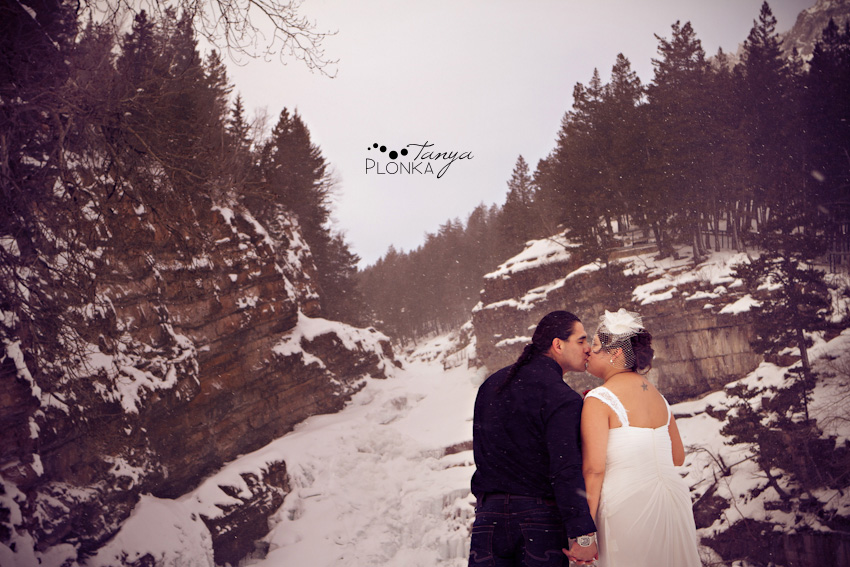 Bride and Groom kiss at Cameron Falls, frozen in the winter