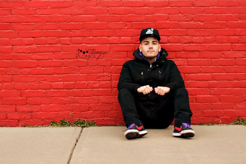 guy sitting against red wall in Lethbridge