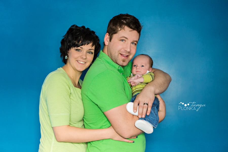 Family holding baby in front of fun blue wall