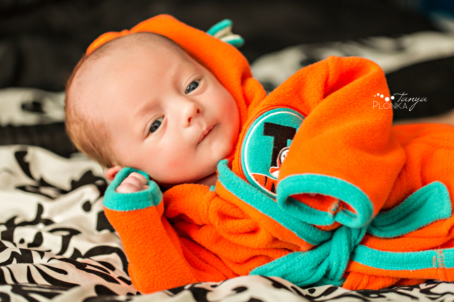 Fun newborn in robe posing on bed