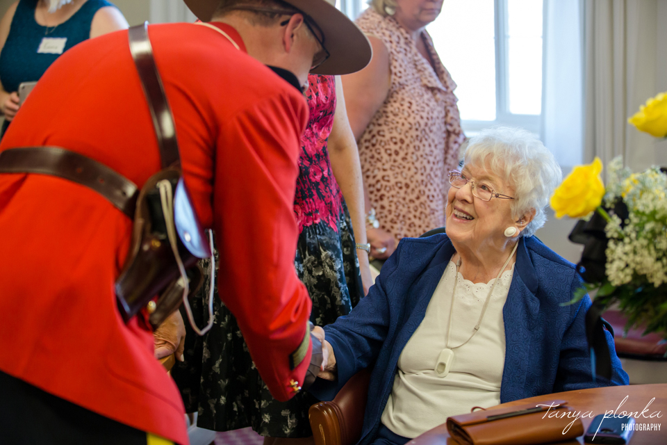 mountie shaking hand of woman who turned 100 years old