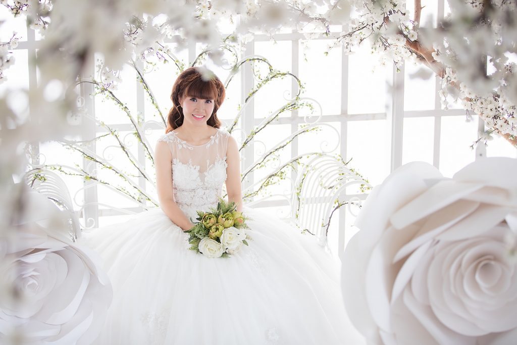 bride sits on white metal throne while smiling at the camera