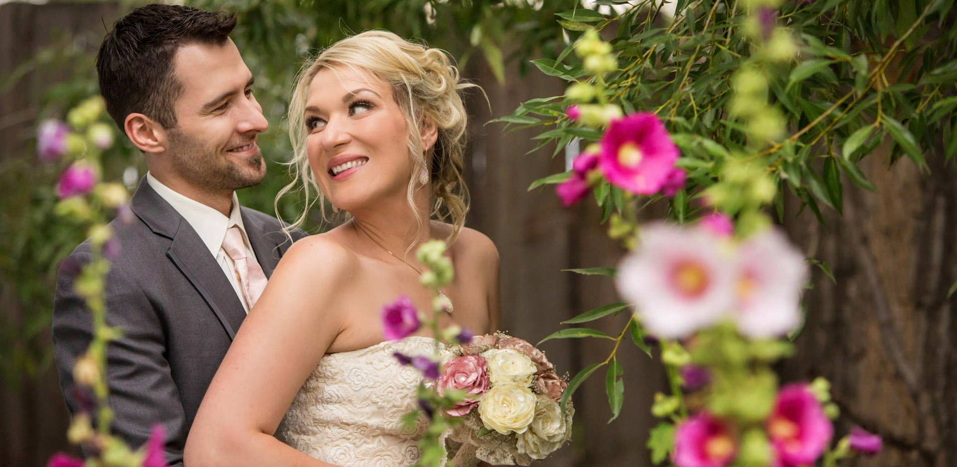 Bride and Groom smiling at each other behind pink hollyhock flowers at the Norland