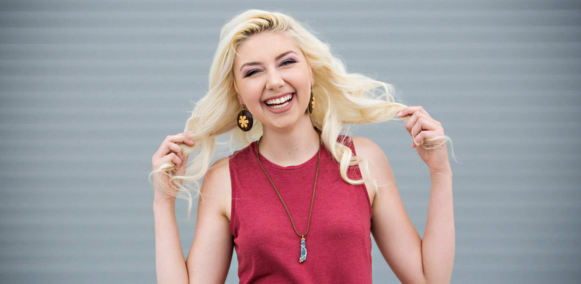 Blonde girl in red shirt laughing in front of gray wall