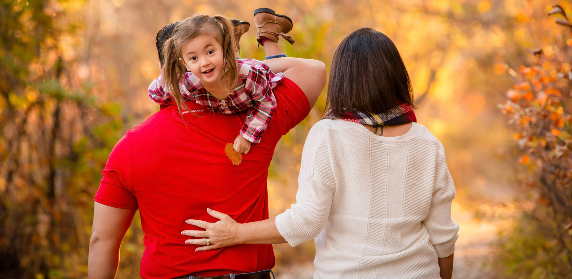 Cute girl being packed away by parents during family photos in autumn in Lethbridge