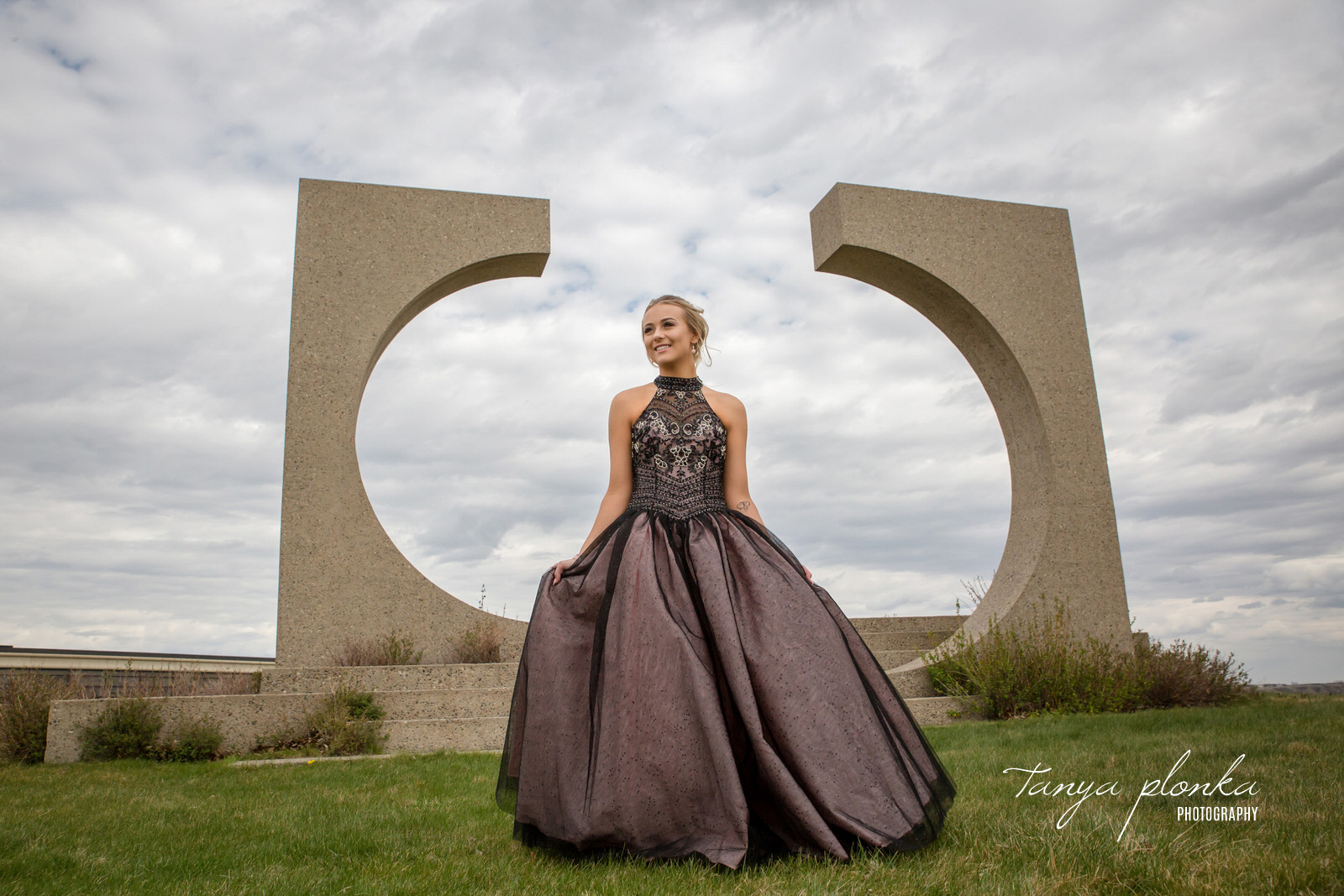 high school grad in purple dress in front of university aperture sculpture