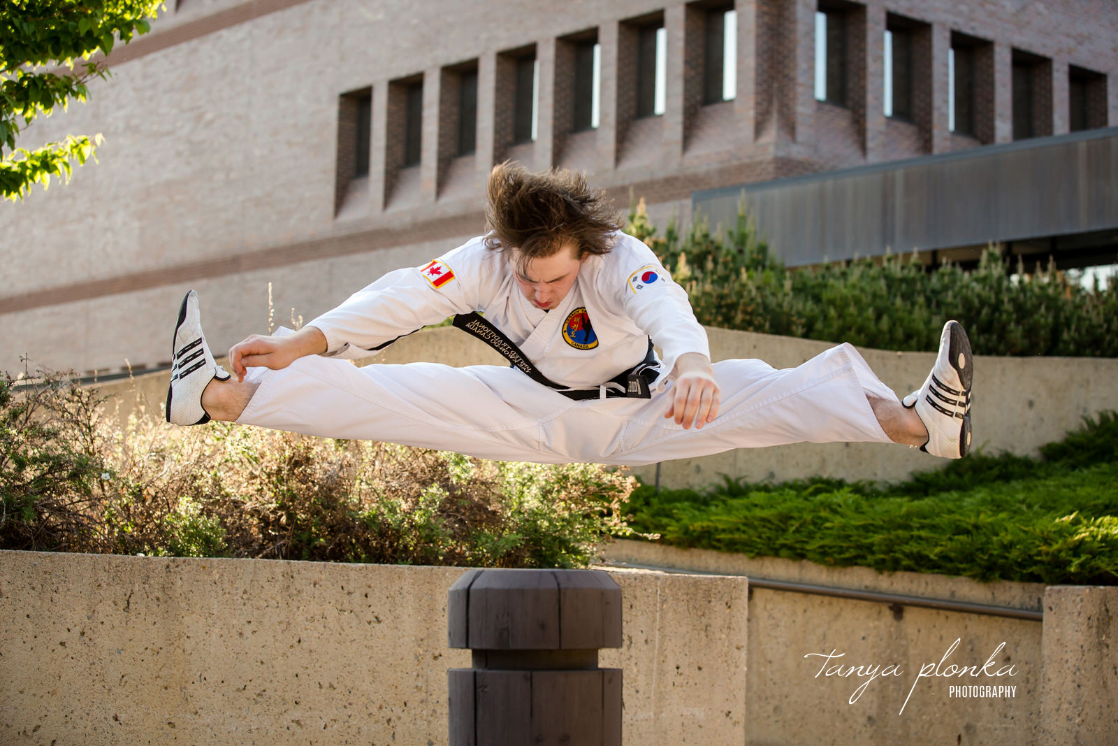 man in Tae Kwon Do uniform jumps over post in splits