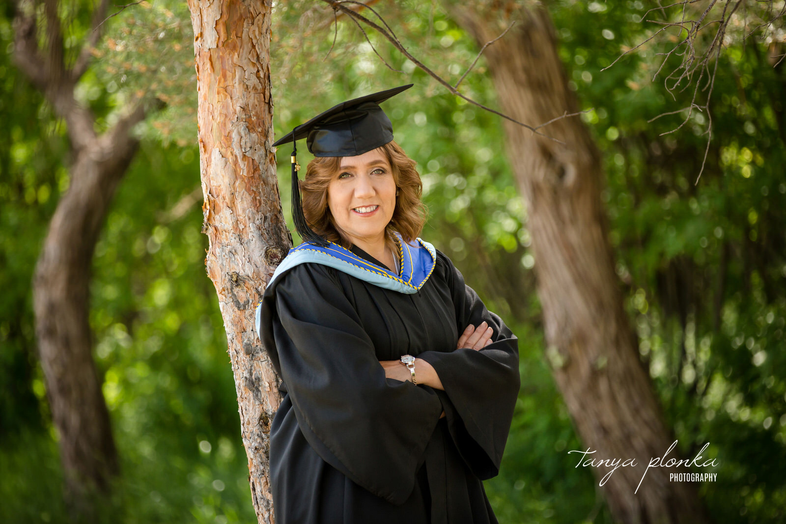 woman in University of Lethbridge cap and gown leans against tree