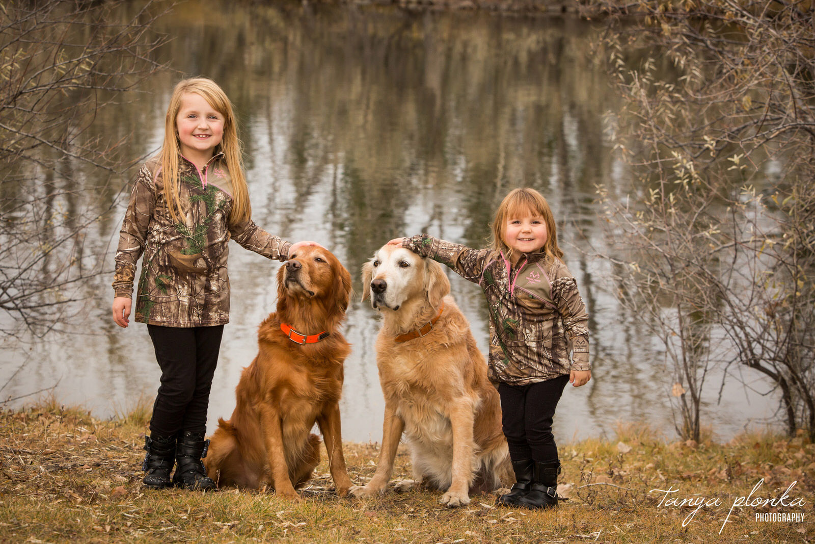 young girls in camo stand next to two golden retrievers at Aperture Park in the autumn