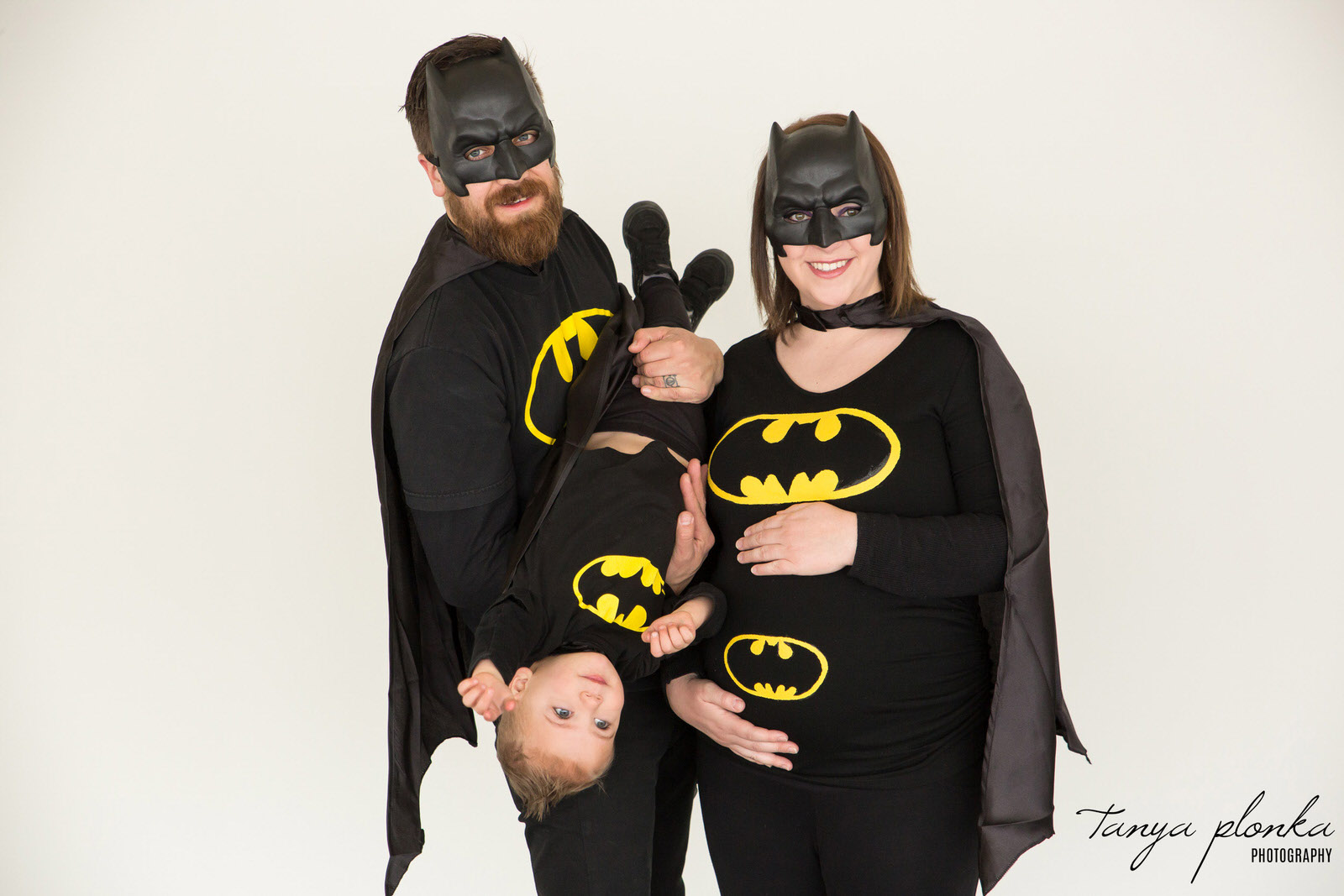 family dressed in Batman outfits pose for maternity photo with toddler held upside down