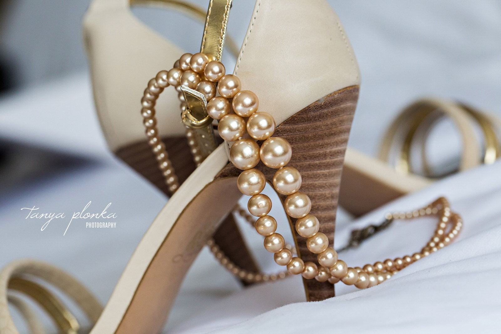 string of champagne pearls over pair of high heel shoes