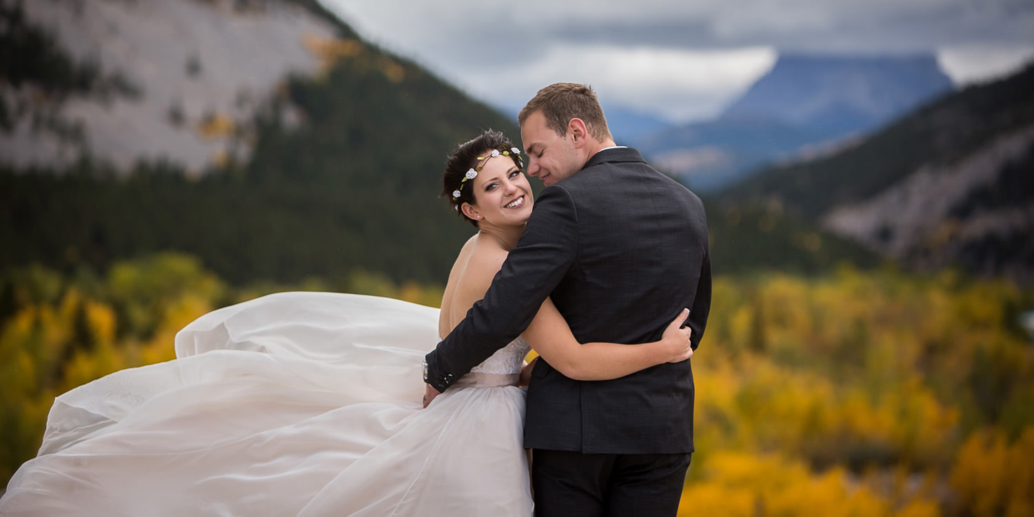 Bride and groom standing in wind, overlooking Crowsnest Mountain in autumn