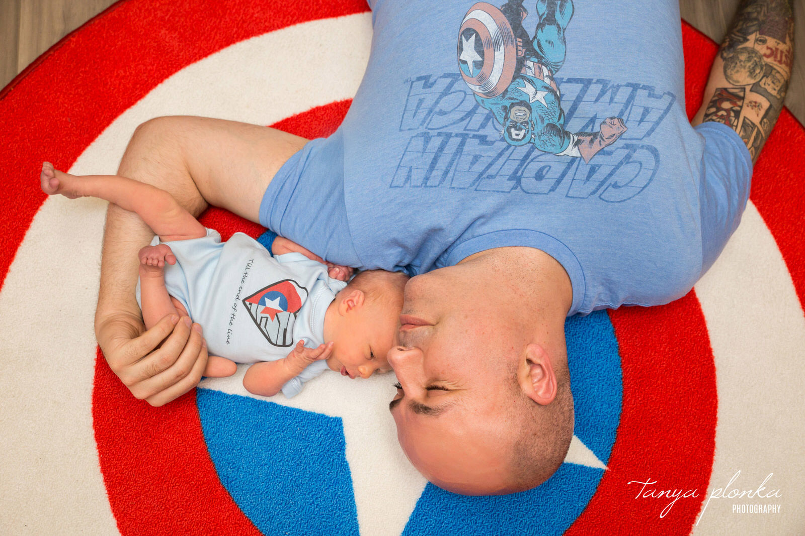 newborn baby with dad both in Captain America t-shirts lay on Captain America shield rug