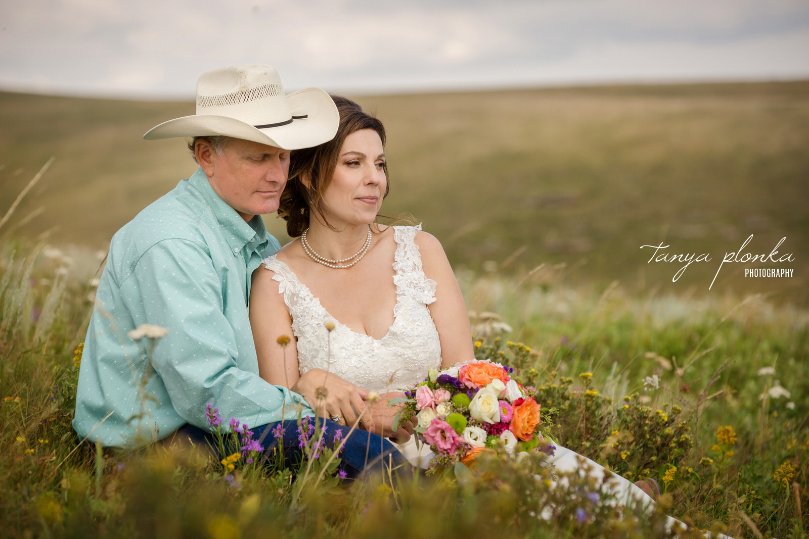 Bride and groom in cowboy hat sit in field of wild flowers
