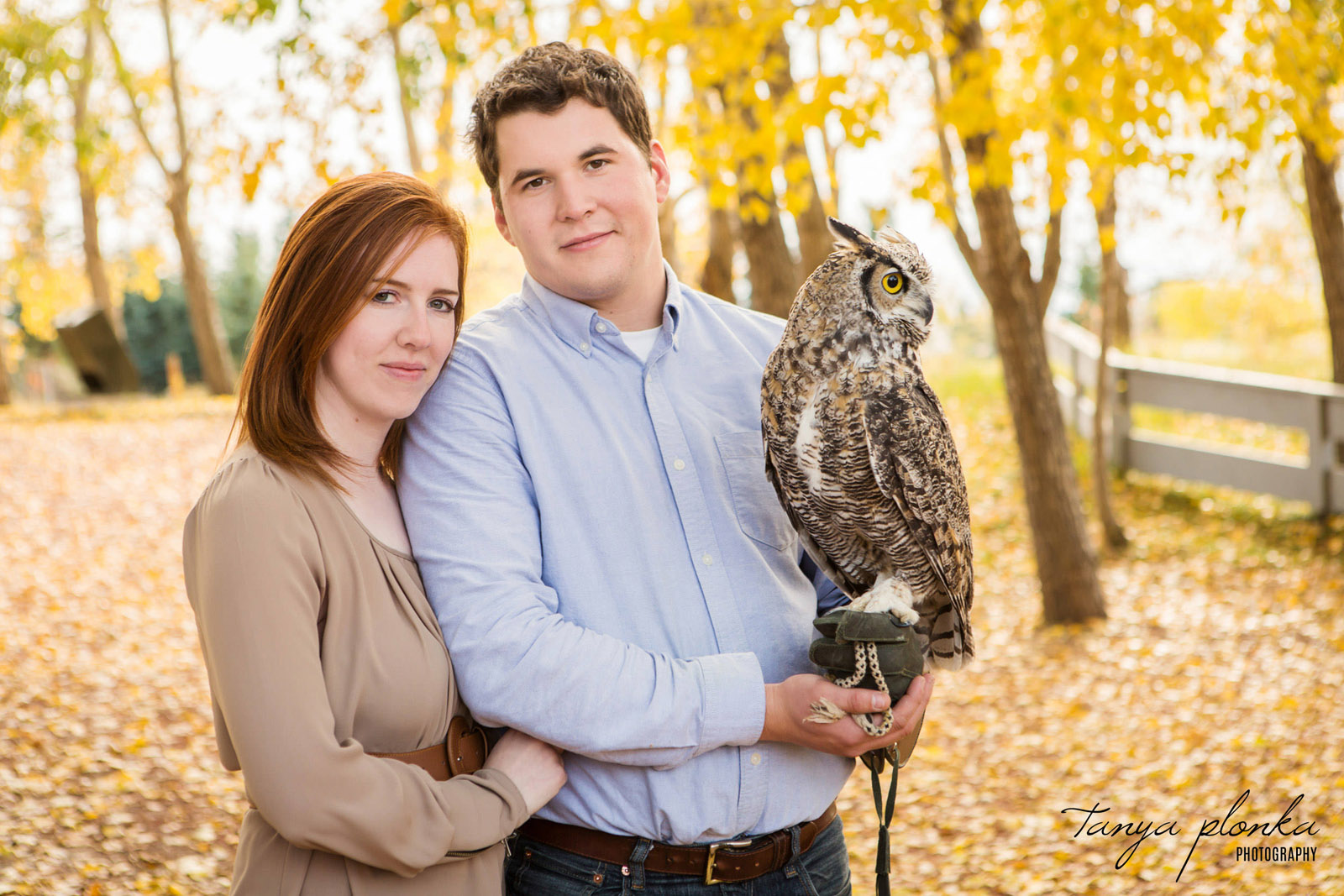couple holds an owl while snuggling at the Coaldale Birds of Prey Centre