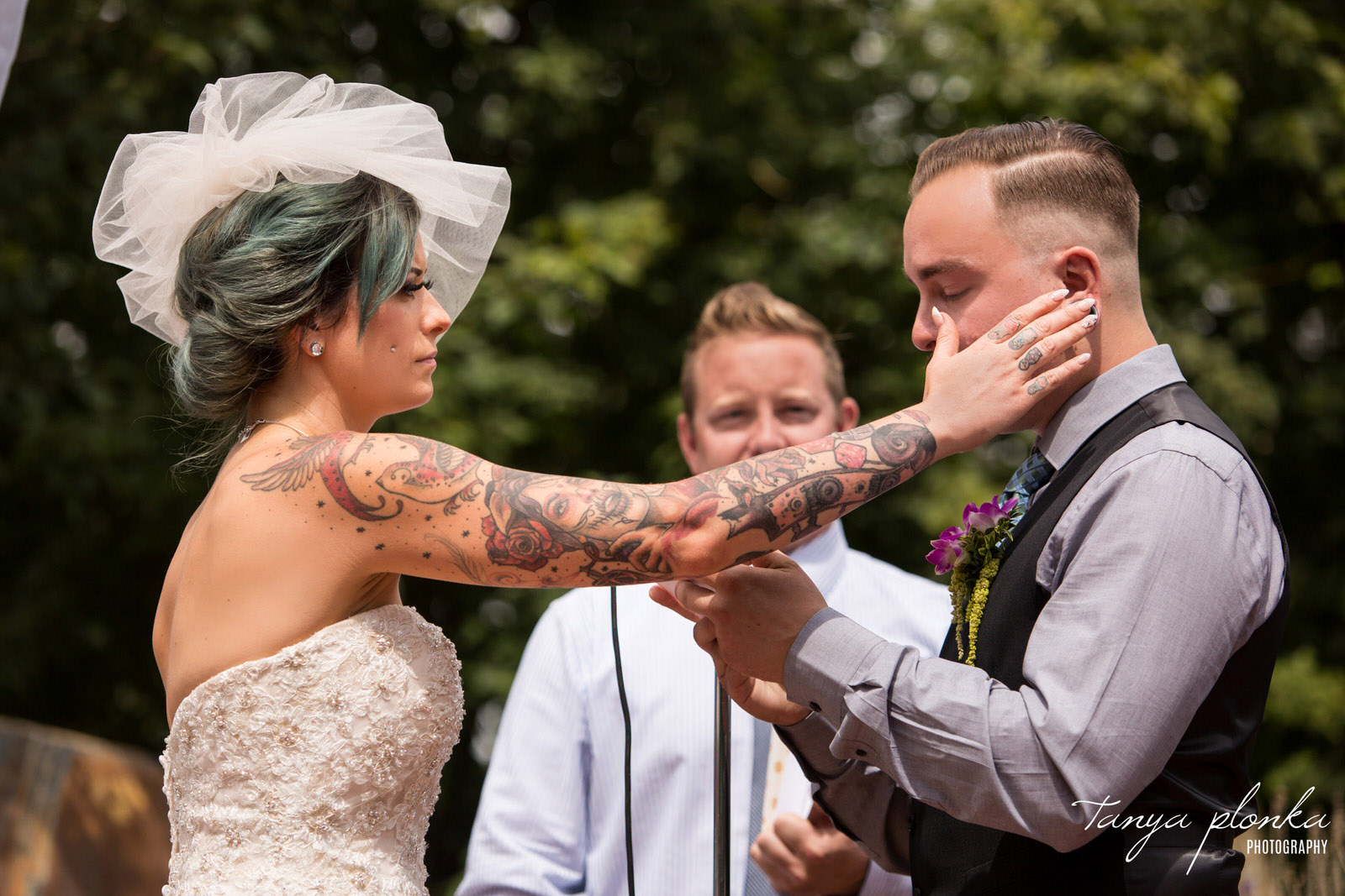 bride with tattooed arm wipes away tear from groom during wedding vows