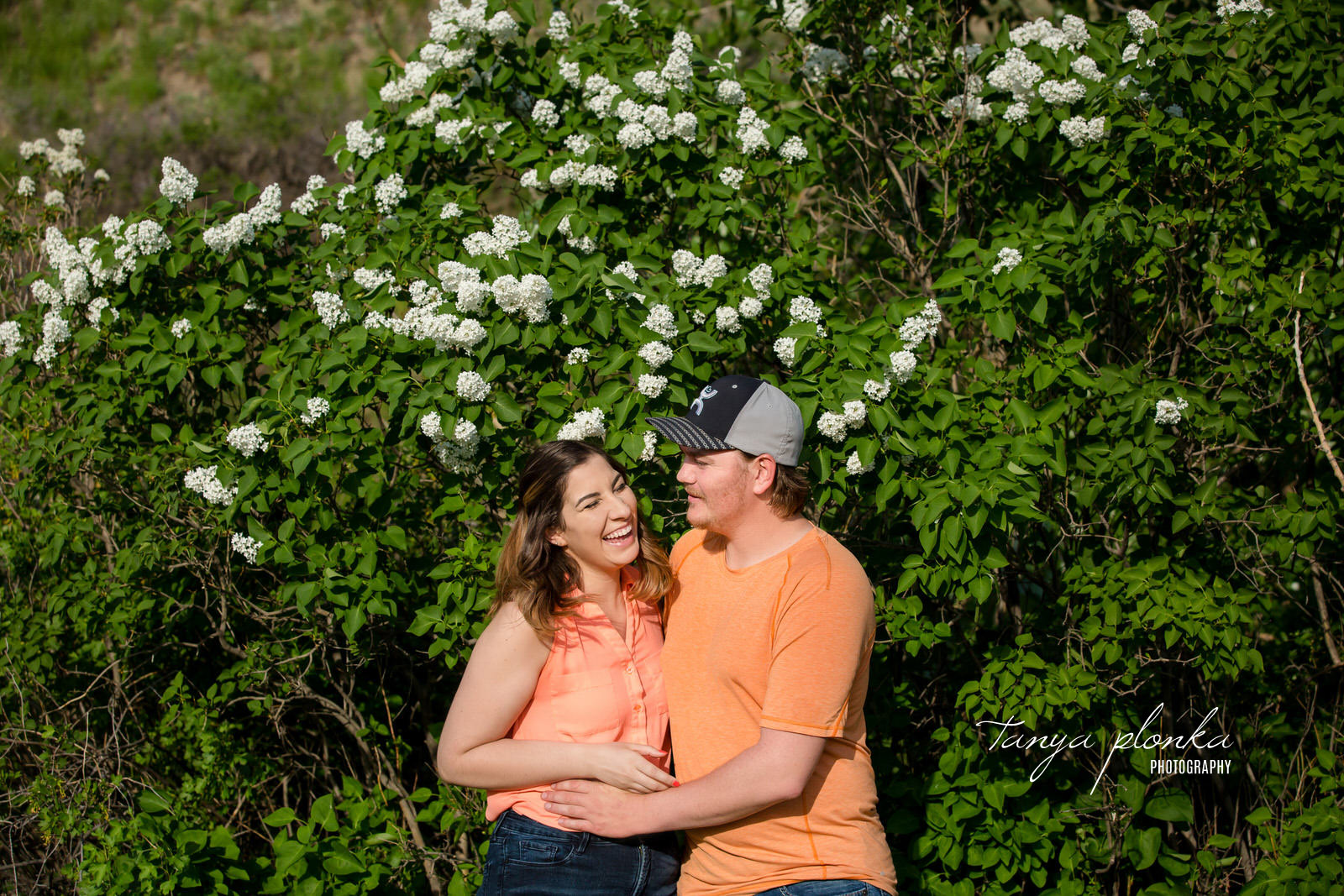 Couple in orange shirts standing in front of Lethbridge white lilacs