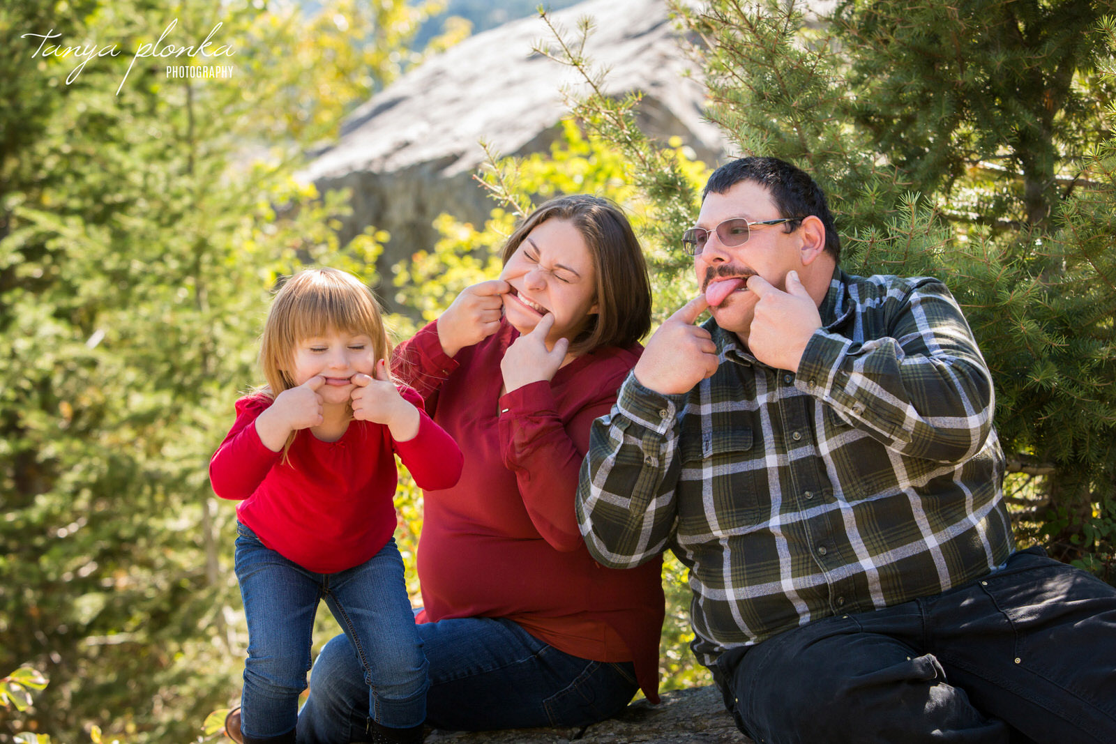 family of three sticks their tongues out at Frank Slide Interpretive Centre