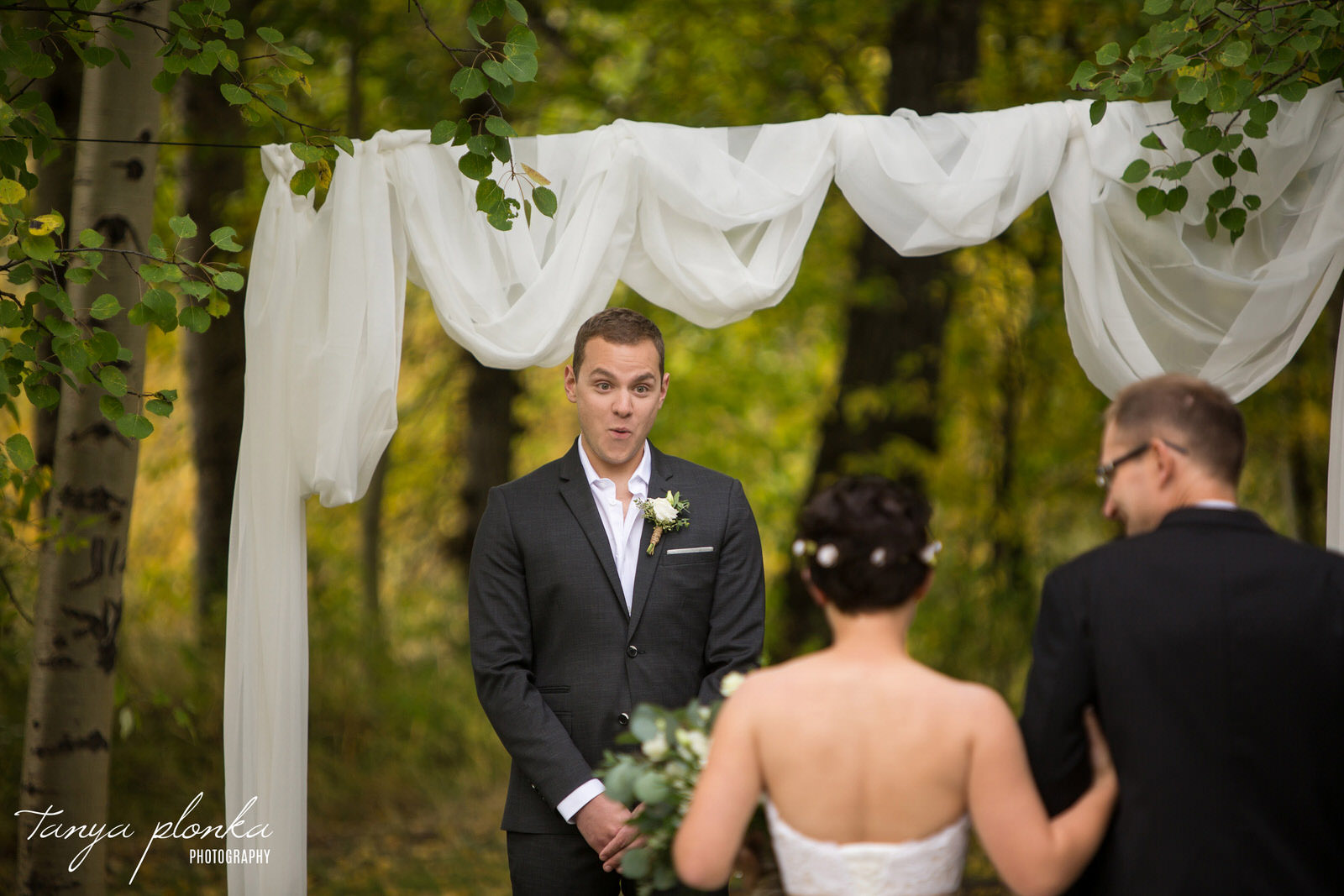 groom looks amazed as he watches bride come down the aisle at wedding ceremony