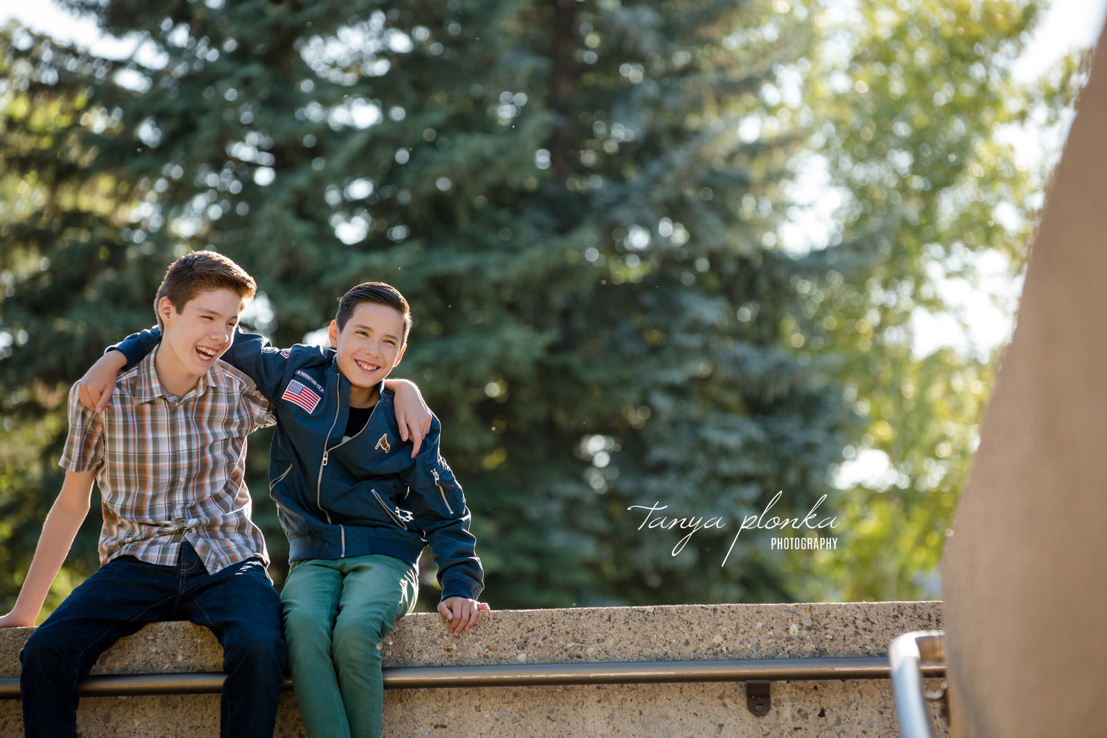 smiling brothers sitting on concrete wall with arm around each other