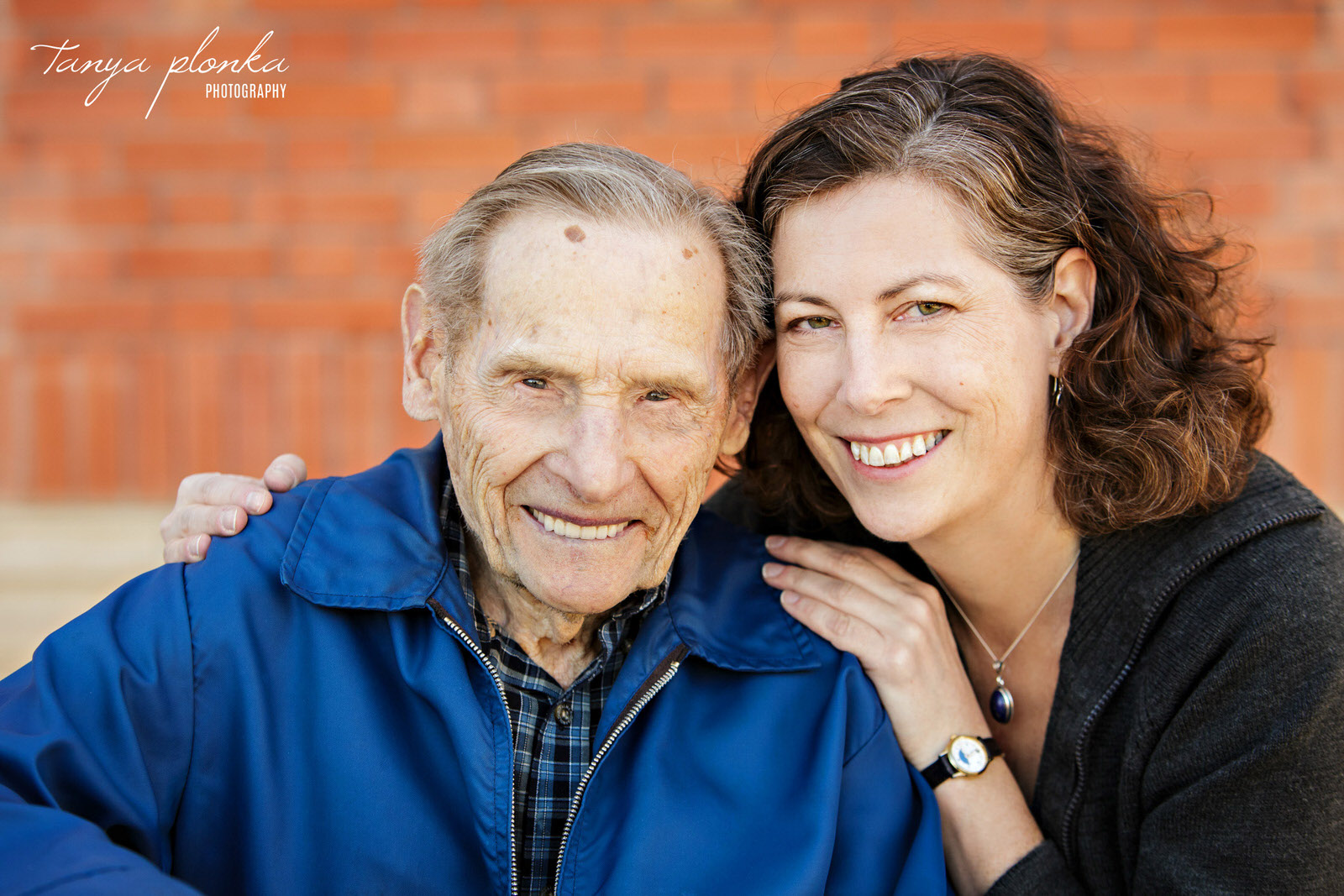 close up photo of woman with her elderly grandfather in front of brick wall
