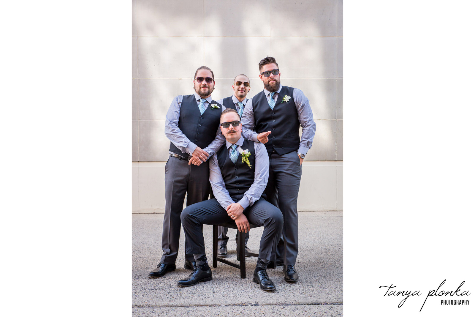 groomsmen pose around groom sitting on chair in alley
