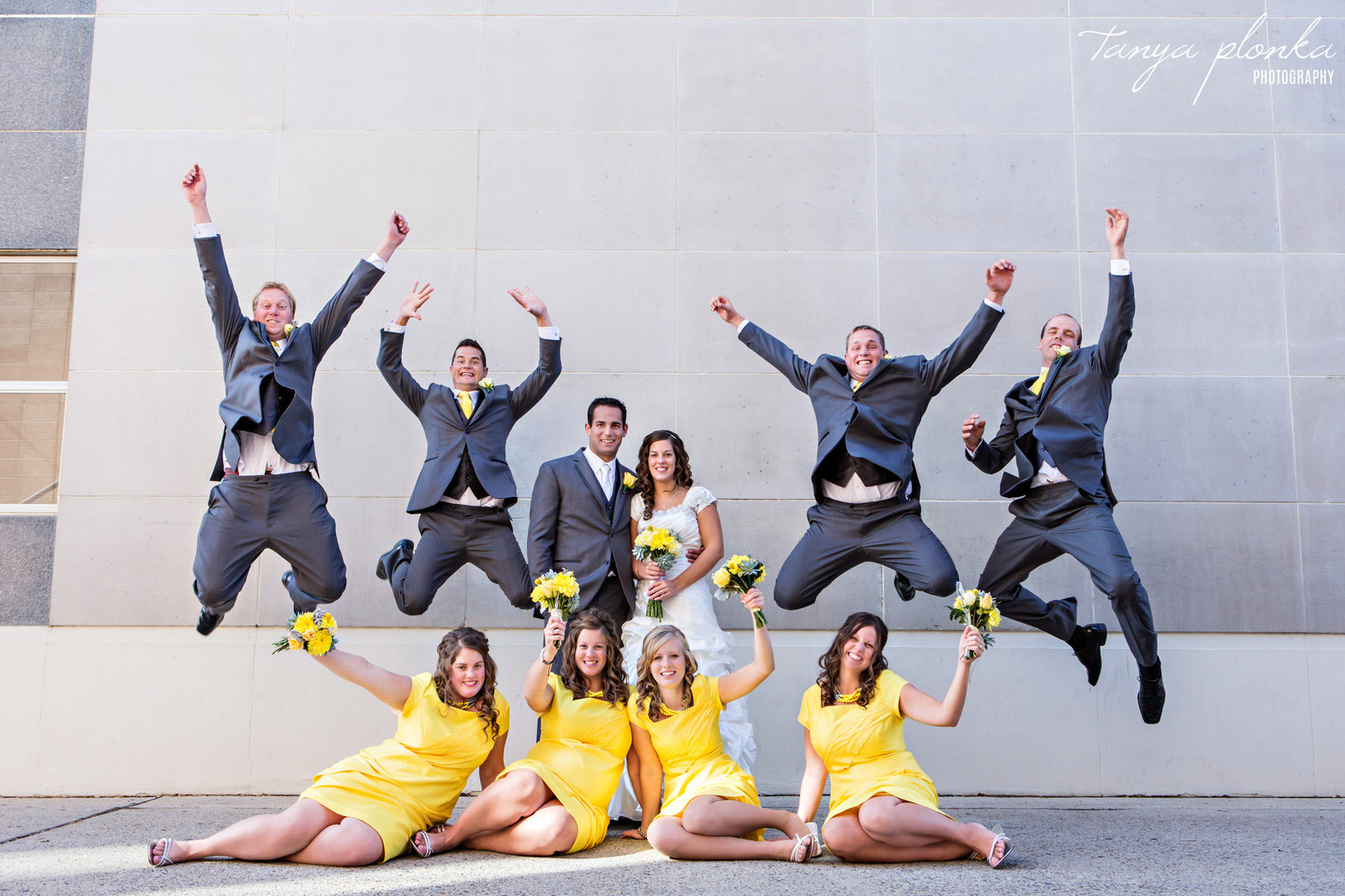 groomsmen jumping in downtown Lethbridge wedding party photo