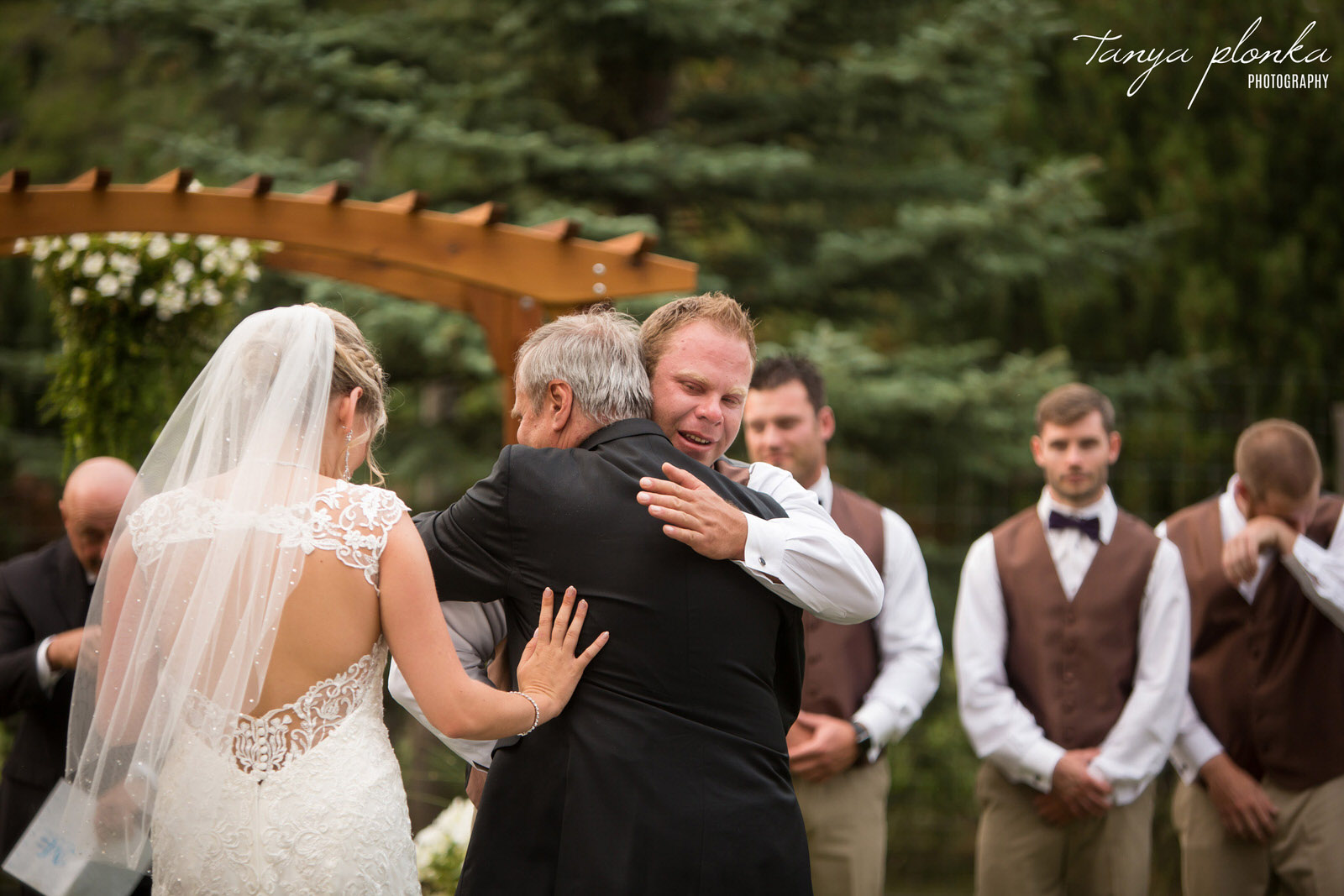 emotional groom hugs bride's dad at wedding ceremony while groomsman in background wipes away tear