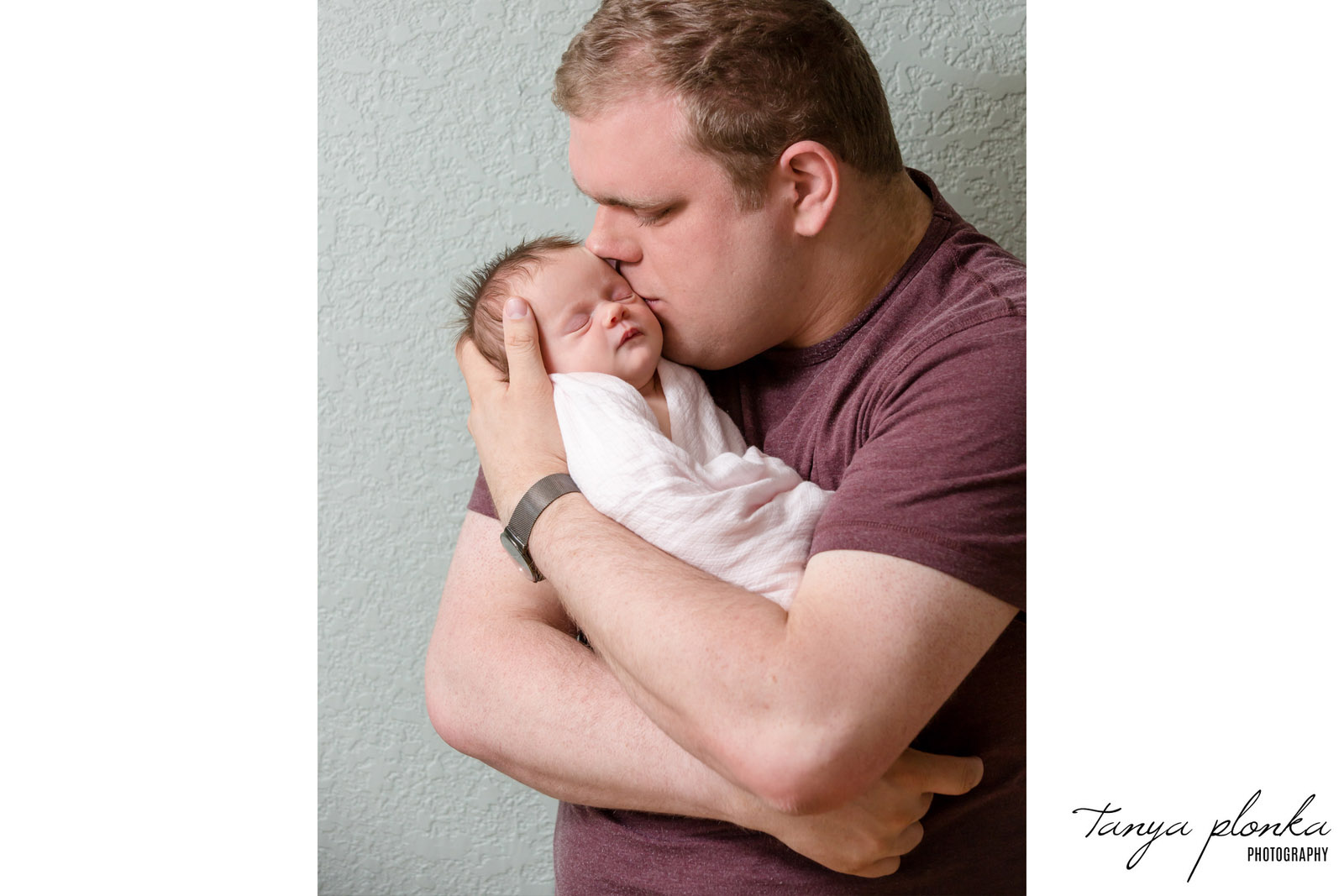 father cradles newborn daughter in arms and kisses her cheek