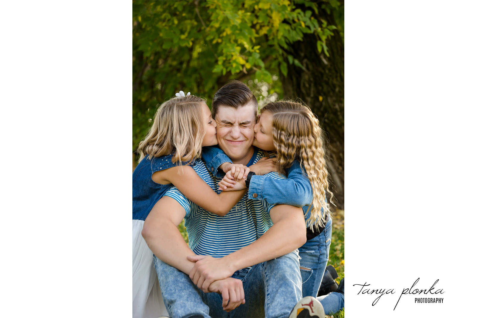 Funny photo of sisters kissing brother's cheeks
