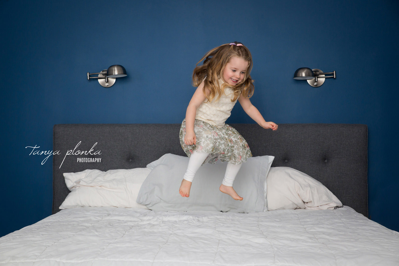 girl jumping on bed in front of blue wall
