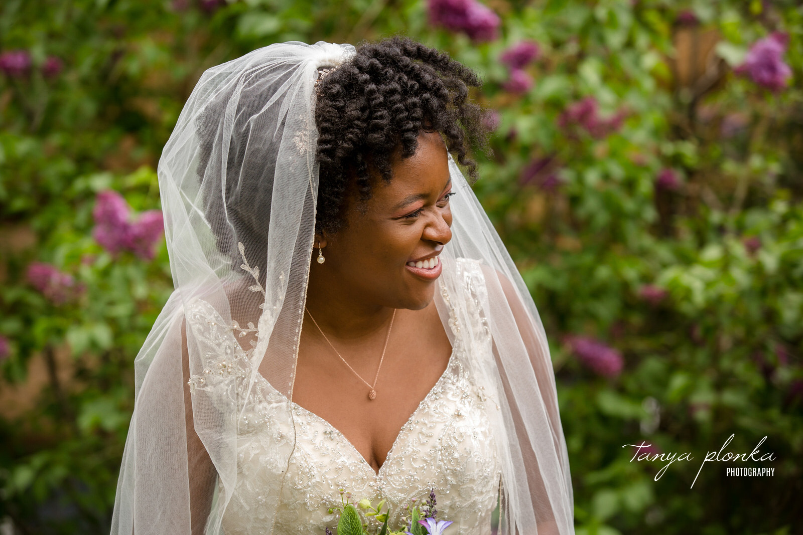 close up photo of bride smiling to right with lilacs behind her