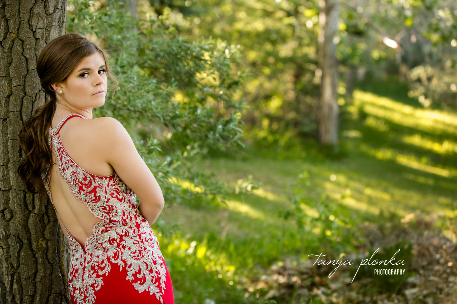 high school graduate in red grad dress with silver sequins looking over shoulder