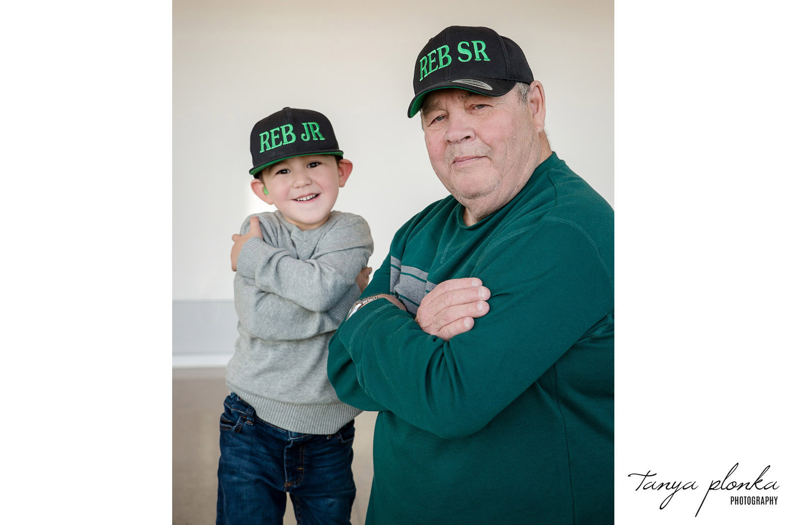 Grandpa and great grandson in matching hats stand with arms crossed