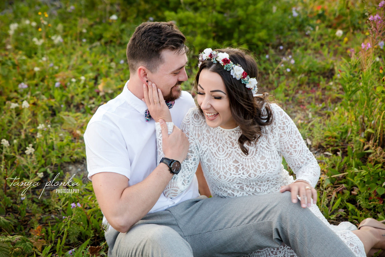 couple sitting on ground snuggling and laughing