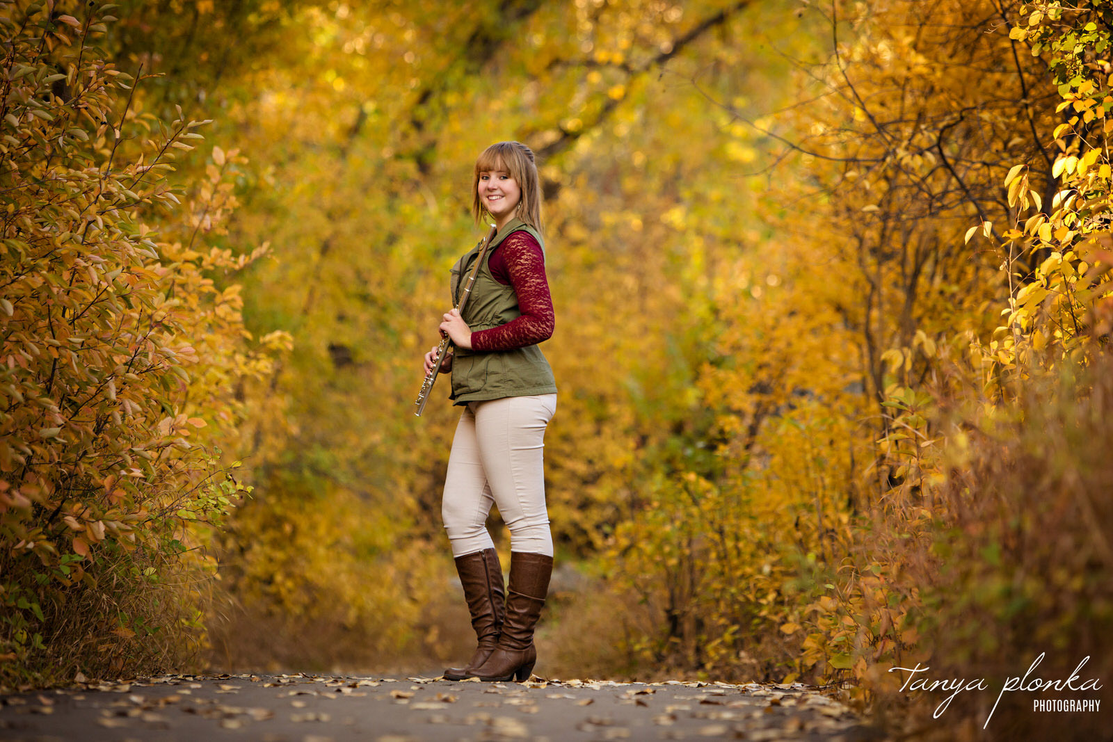 woman holding flute stands in beautiful autumn scene in the Helen Schuler Nature Reserve