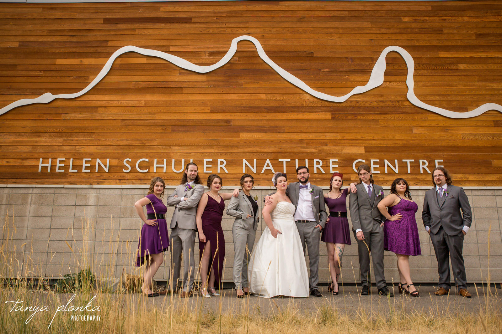 wedding party dressed in gray and purple stand in line outside of the Helen Schuler Nature Centre with serious expressions