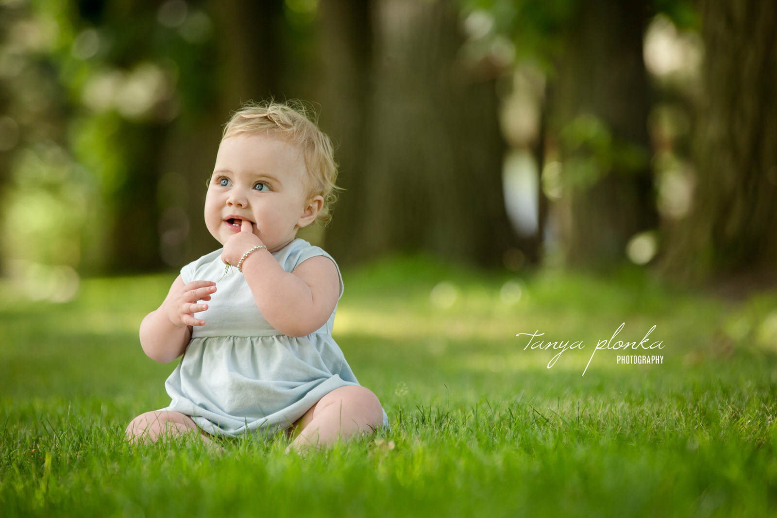 Little girl sits in grass with finger in mouth