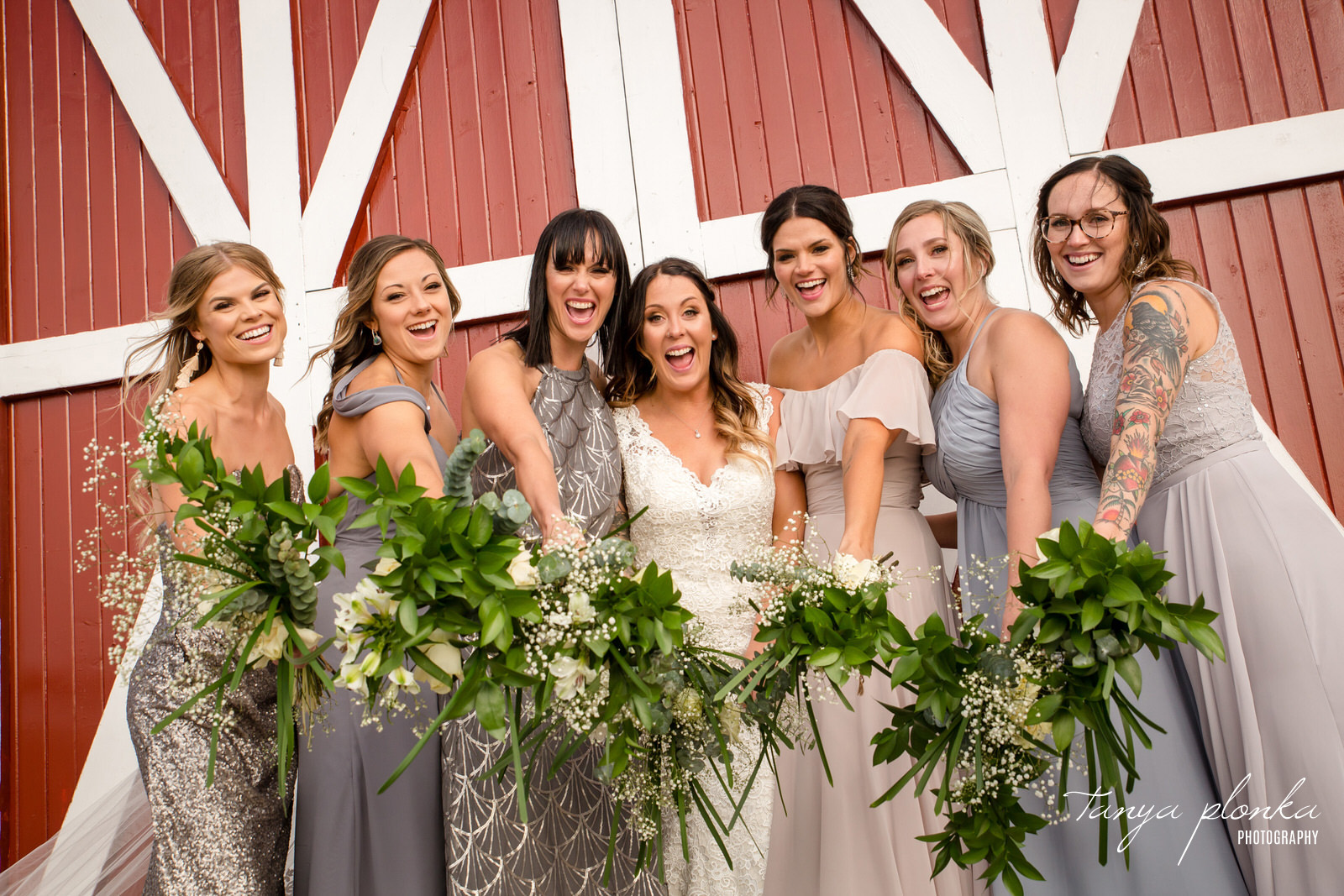 bridesmaids and brides hold bouquets towards camera in front of red barn doors