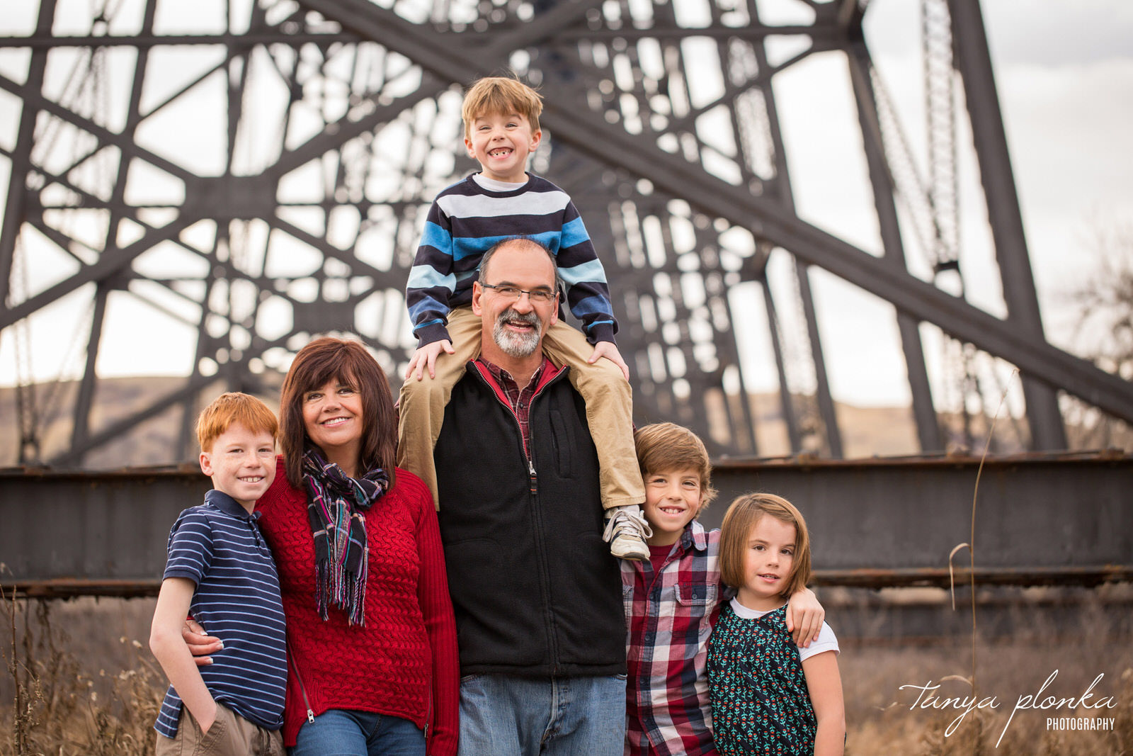 grandparents stand in front of high level bridge with their four grandchildren