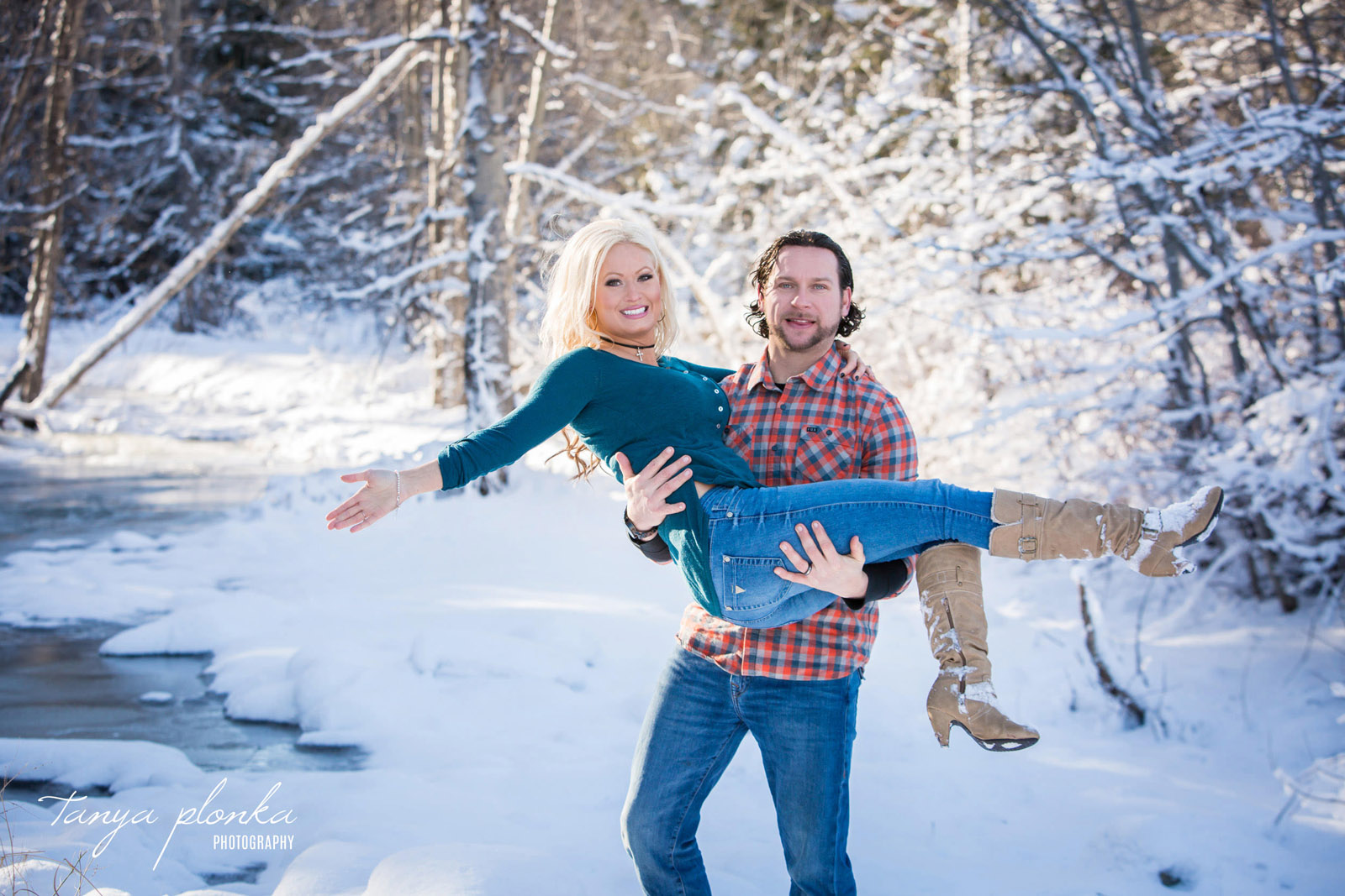 husband lifting happy wife in snowy winter Hillcrest landscape