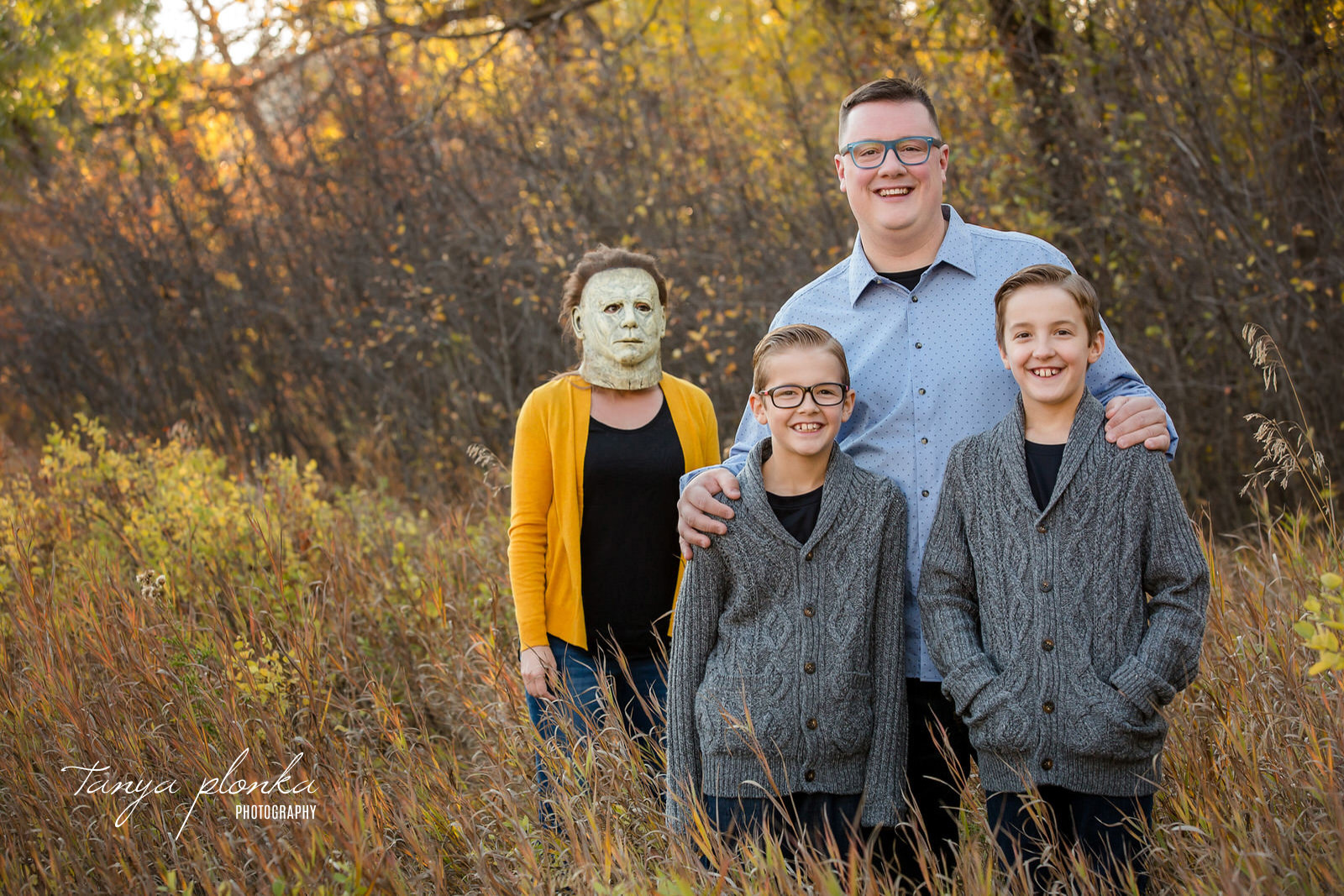 Family poses smiling while mom wearing Jason mask stands behind them