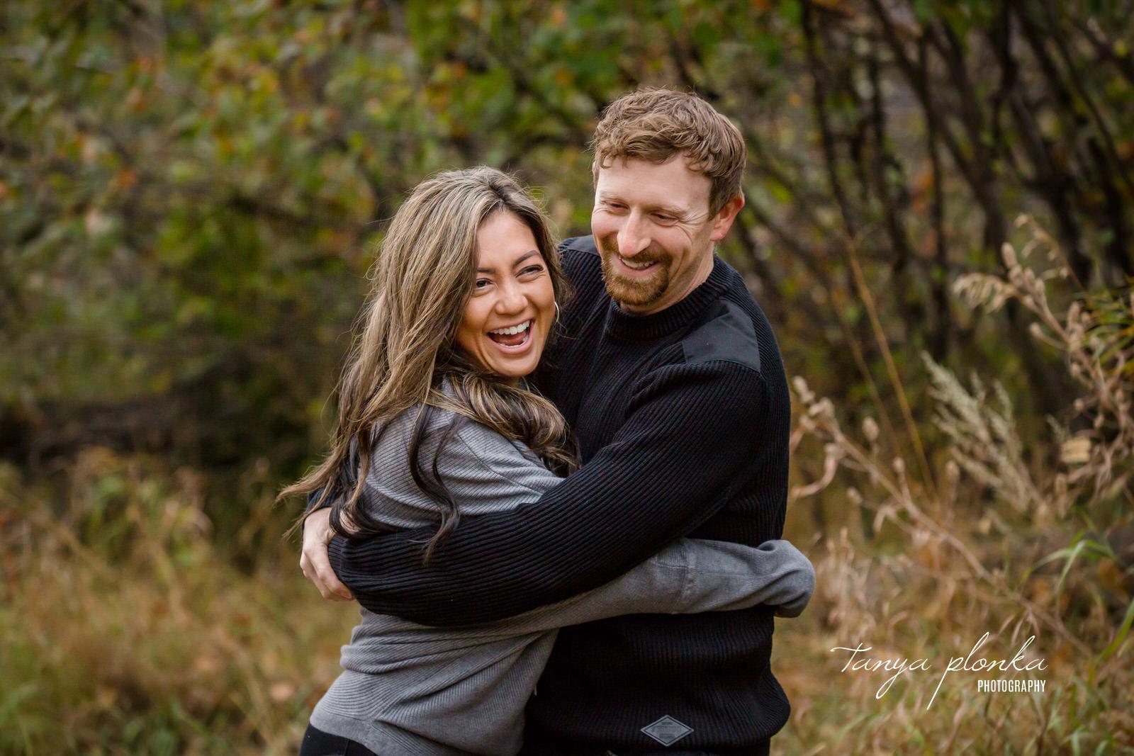 Hugging couple laughing in Lethbridge river bottom
