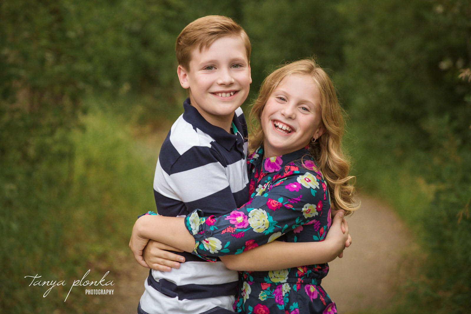 young brother and sister hug while smiling at the camera