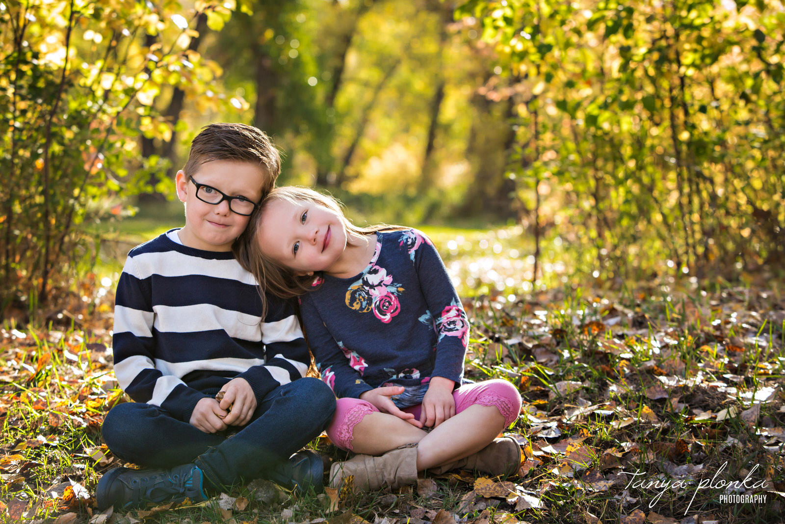 sister rests head on brother's shoulder while they sit cross legged in Indian Battle Park