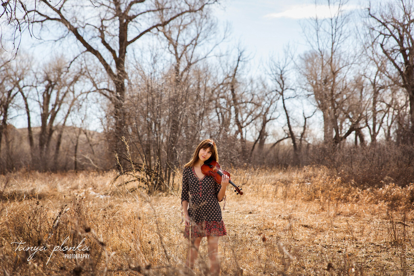 woman holding violin stand in Indian Battle Park in the early spring
