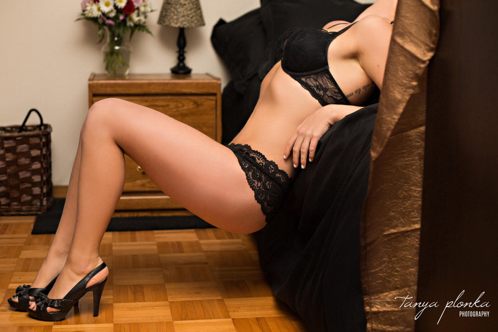 cropped photo of woman leaning on bed in black lace lingerie